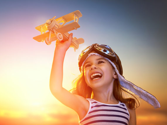 Image of a happy little girl holding a toy airplane